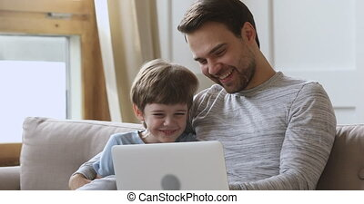 Funny cute kid son learning using laptop laughing with dad