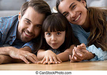 Funny cute little daughter lying on warm floor with parents, por