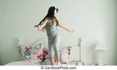 Funny cute little girl in wireless headphones dancing and have fun in holiday morning jumping on bed at home in cozy light bedroom