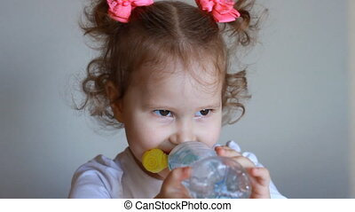 Funny cute little girl is drinking water from a bottle....
