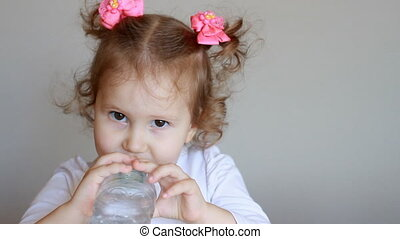 Funny cute little girl is drinking water from a bottle. Child and thirst. The baby takes a sip of the drink close up.