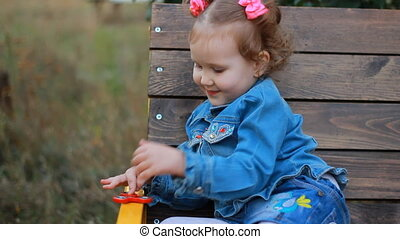 Funny cute little girl is playing with a spinner in the park on a bench.