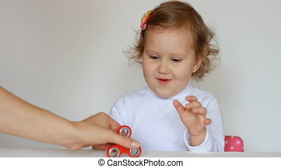 Funny cute little girl is playing with a spinner on a light background. Close-up.