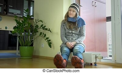 funny cute woman undressing cap sitting on radiator heater....