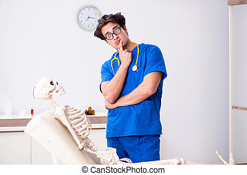 Funny doctor with skeleton in hospital