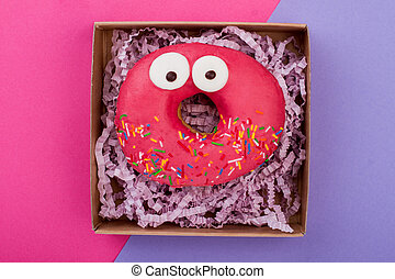 Funny donut in box, top view.