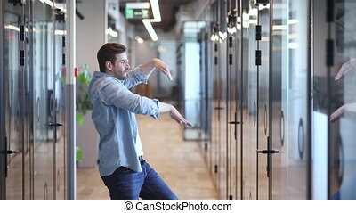 Funny excited happy business man employee winner triumphant dancing in slow motion in office hallway alone having fun celebrate business success reward corporate promotion in victory dance concept