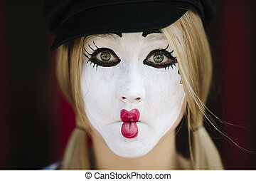 funny face - Female Mime on red background, selective focus