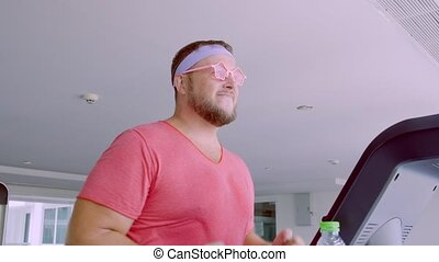 Funny fat male in pink glasses and in a pink t-shirt is...