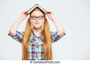 Funny female student with book on head
