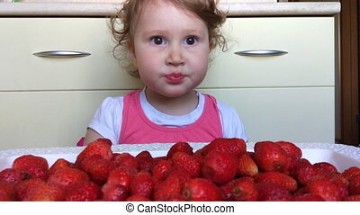 Funny funny girl eating strawberries. A child is eaten by a...