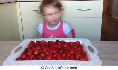 Funny funny girl eating strawberries. A child is eaten by a summer berry