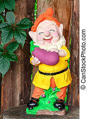 Funny garden dwarf with eggplant
