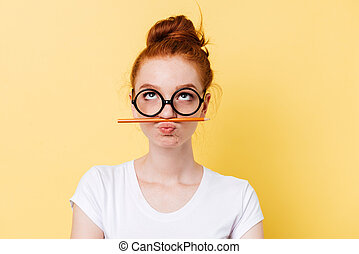 Funny ginger woman in eyeglasses playing with pencil