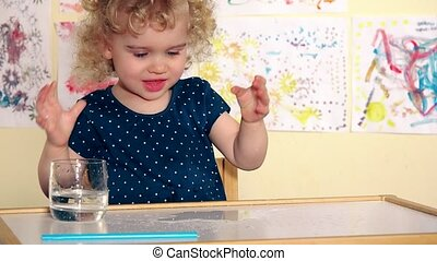 Funny girl child pour water on table and spatter it with...