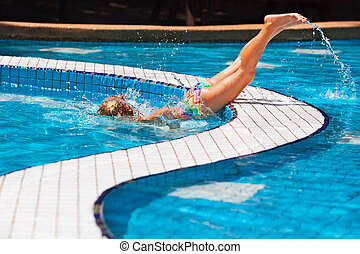 Funny girl diving underwater in swimming pool