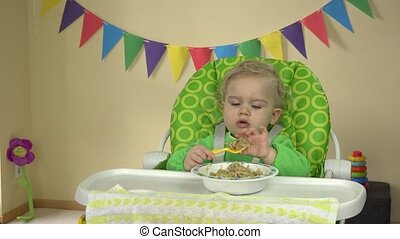 Funny girl eat porridge with spoon and hands sitting in baby feeding chair.