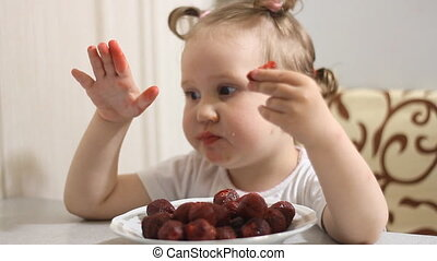 Funny girl eats berries strawberries.