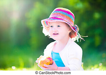 Funny girl in a hat eating apple