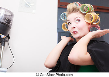 Funny girl in curlers at hair salon