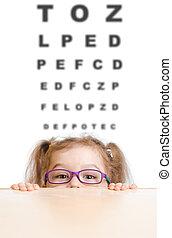 Funny girl in eyeglasses with eye chart