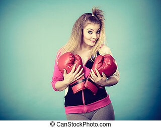 Funny girl in red gloves playing sports boxing