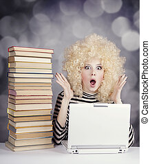 Funny girl in wig with notebook and books. Studio shot.