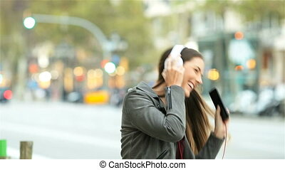 Funny girl listening to music singing and dancing