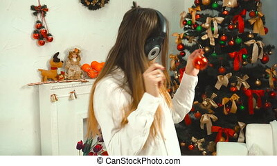 funny girl listens to music with headphones and decorates a Christmas tree