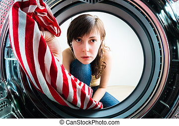 Funny girl loading clothes to washing machine