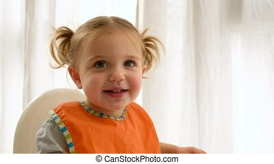 Cute toddler with bib and ponytails looking at camera while sitting in high chair during lunch at home