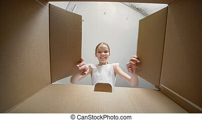 funny girl looks in the box, is surprised.