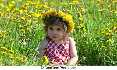 Funny girl on dandelion field in sunny day
