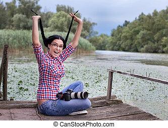 Funny girl photographer on the lake - Beautiful young woman...