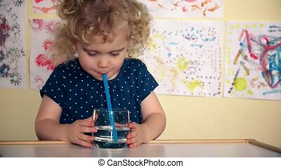 Funny girl play with straw and glass of water sitting by table in her room
