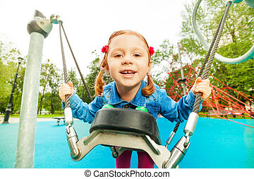 Funny girl portrait on swing set of playground