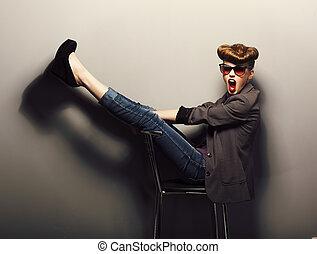 Funny delightful girl sitting in sunglasses on chair in studio