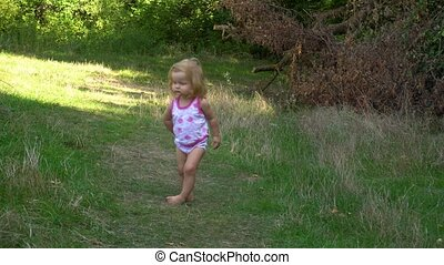 Funny girl walking on path towards camera - Cute little girl...