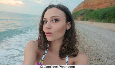 Funny girl wearing a bikini records selfie video on camera...