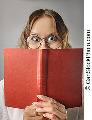 Funny girl with a book in glasses.