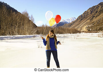 Funny girl with balloons on the hair on the background of snowy