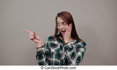 Young brunette girl blue green in checked shirt on grey background funny girl with glasses reacts to fact, points her index finger to side