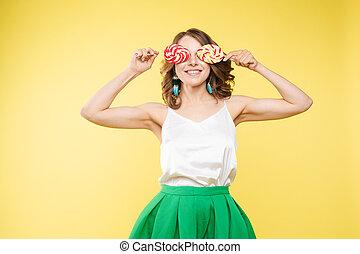 Funny girl with lollipops on eyes and open mouth.