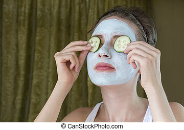 funny girl with mask holding two cucumber on the eyes