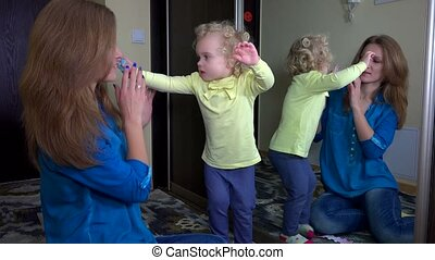 Funny girl with pin in hair with her mother in front of...