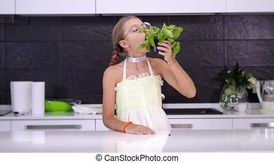 Funny blonde teenage girl in stylish dress with plaits eats fresh mint growing in pot standing at table in brightly lit kitchen