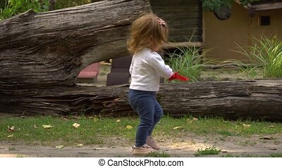 Funny girl with sand shovel walking in park - Adorable...