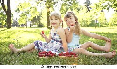 Funny girls eating strawberries.