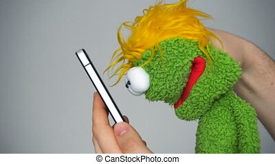 Funny green puppet looking in smartphone and laughing