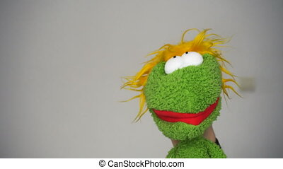 Funny green puppet talking and looking in camera